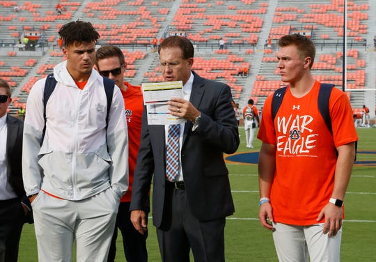 Auburn coach Gus Malzahn goes through preparations with quarterbacks Joey Gatewood (left) and Bo Nix (right) before a game against Mississippi State on Sept. 28, 2019.
