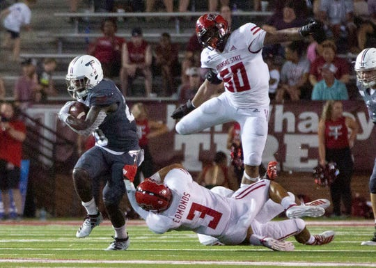Troy running back DK Billingsley (20) keeps running as Arkansas State's B. J. Edmonds (3) tries to bring him down.