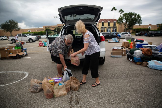Ron Seppa and Cindy Seppa unload donations from their car during a Bahamas Disaster Relief event at the Miromar Outlet Mall on Sunday, September 29, 2019, in Bonita Springs.