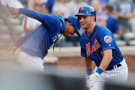 New York Mets' Joe Panik, right, celebrates with Marcu Stroman after hitting a solo home run during the eighth inning of a baseball game against the Atlanta Braves, Sunday, Sept. 29, 2019, in New York. (AP Photo/Kathy Willens)