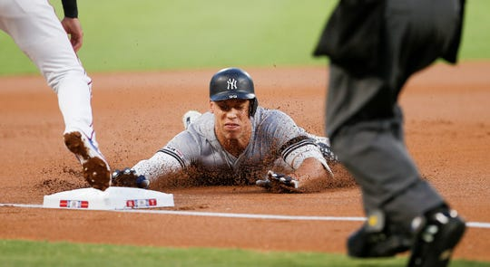 New York Yankees' Aaron Judge (99) dives into third on a triple during the first inning of a baseball game against the Texas Rangers, Saturday, Sept. 28, 2019, in Arlington, Texas.