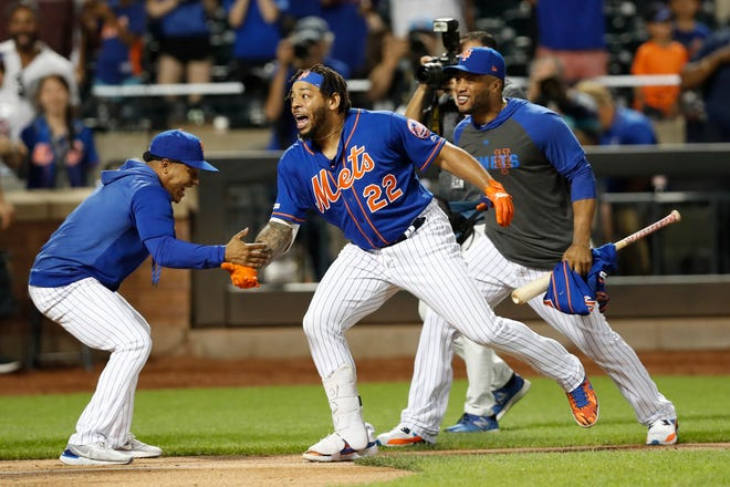 New York Mets' Marcus Stroman, left, greets Dominic Smith (22) at the plate after Smith hit a walk-off, solo home run in a baseball game against the Atlanta Braves, Sunday, Sept. 29, 2019, in New York. Mets Robinson Cano joins the celebration, right. (AP Photo/Kathy Willens)