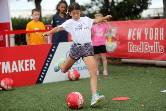 Olivia Pesso, 11, of Waiting River, NY, kicks a soccer ball outside Red Bull Arena, before, Sky Blue FC took on the Orlando Pride.  The game was moved to Harrison to accommodate the amount of fans that wanted to see the game.  The game, which normally would take place at Yurcak Field, where the capacity is approximately 5,000 fans, had more than 8,300 in attendance in Harrison. Pesso came to the game with her parents and sister. Sunday, September 29, 2019