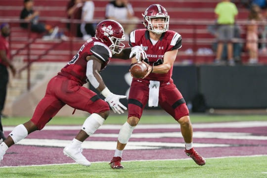NMSU redshirt sophomore quarterback Josh Adkins (14) hands off the ball as New Mexico State University Aggies face off against the Fresno State Bulldogs at Aggie Memorial Stadium in Las Cruces on Saturday, Sept. 28, 2019.