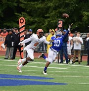 Catholic Central wide receiver Jonathan Brewer attempts for a catch over Brother Rice senior cornerback  Jonathan Tillman.