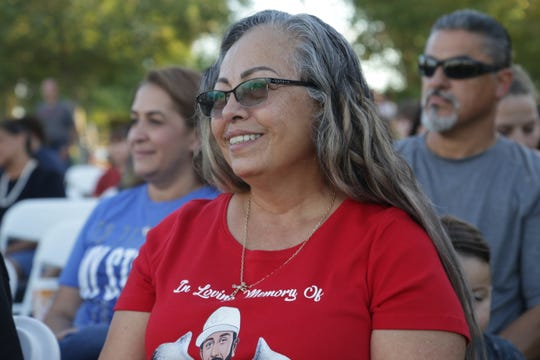 Kathy Gallegos, whose son was killed at a McDonald's in Phoenix in February, smiles while listening to speakers on Sept. 28, 2019. Gallegos said her strong Catholic faith is what keeps her moving forward.