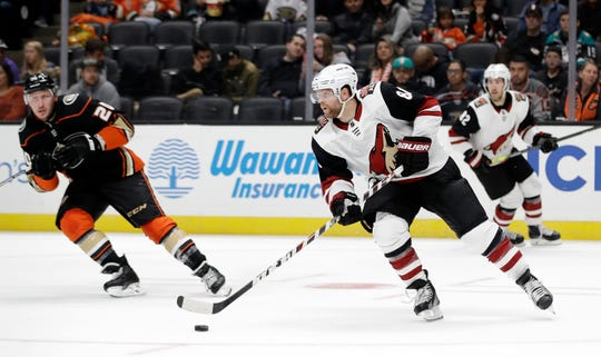 Arizona Coyotes' Phil Kessel, left, controls the puck in front of Anaheim Ducks' Nicolas Deslauriers, left, during the second period of a preseason NHL hockey game, Saturday, Sept. 28, 2019, in Anaheim, Calif.