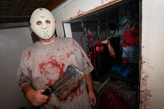 "Anthony Taylor, who plays the butcher in the Decades of the Dead haunted house at the Yale Hotel, poses for a photo outside the attraction's ""meat locker"" Saturday, Sept. 28, 2019."