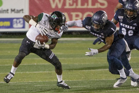 Hawaii receiver JoJo Ward (9) is grabbed by Nevada's Berdale Robins during Saturday's Mountain West game at Mackay Stadium.
