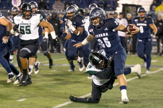 Nevada running back Toa Taua (35) is grabbed  by Hawaii's Cortez Davis during  the first half of Saturday night's game.