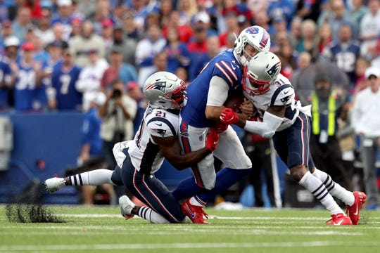 Duron Harmon, left,  and Jonathan Jones, right, of the New England Patriots tackle Josh Allen of the Buffalo Bills during the fourth quarter at New Era Field on September 29, 2019 in Orchard Park, New York. Allen left the game with a concussion after this play.