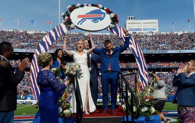 Mackenzie Park and Jordan Binggeli cheer after being married at midfield during halftime of an NFL football game between the Buffalo Bills and the New England Patriots, Sunday, Sept. 29, 2019, in Orchard Park, N.Y. (AP Photo/Adrian Kraus)