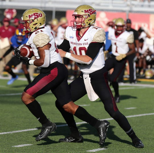 Midwestern State University quarterback Zach Purcell hands the ball off to running back Quinton Childs during a Lone Star Conference game against Angelo State at LeGrand Stadium at 1st Community Credit Union Field Saturday, Sept. 28, 2019. ASU won 28-6.