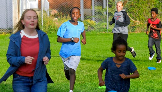 In this Sept. 11, 2019, photo Salman Yusuf, second from left, and others run laps on the field at Ellis Elementary School in Logan, Utah. Yusuf, who is a refugee from Somalia, is one of many kids who participate in the after school running club. (Eli Lucero/The Herald Journal via AP)