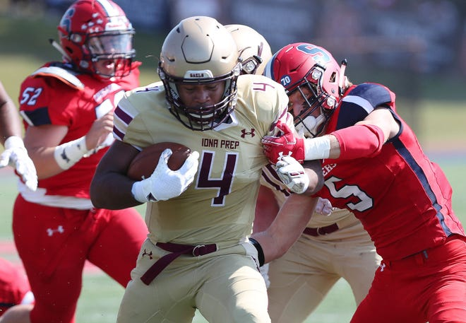 Iona's Frankie McFadden (4) breaks away from Stepinac defenders during action at Stepinac High School in White Plains Sept. 28, 2019.  Iona won the game 36-35.