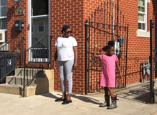 Yvette Forrest and her 8-year-old daughter watched on Sunday as a broad-based coalition of faith, nonprofit and community groups marched for peace in Wilmington.