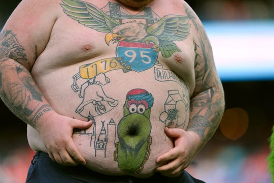 A fan of the Philadelphia Phillies shows off his Phillie Phanatic tattoo during a game against the Miami Marlins at Citizens Bank Park on September 29, 2019 in Philadelphia, Pennsylvania. The Marlins defeated the Phillies 4-3.