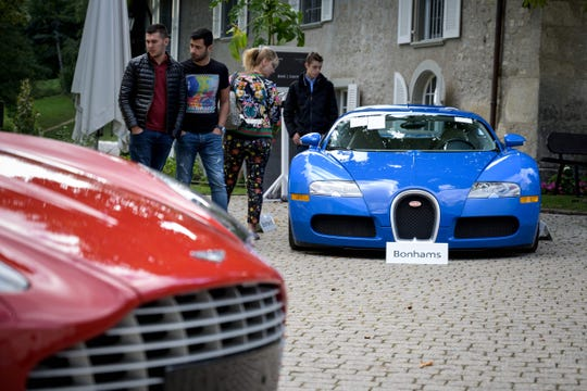 A picture taken on September 28, 2019 at the Bonmont Abbey in Cheserex, western Switzerland shows a 2010 Bugatti Veyron EB 16.4 Coupe model car (R) and a 2011 Aston Martin One-77 Coupe model car during an auction preview by sales house Bonhams of sport cars belonging to the son of the Equatorial Guinea's President.