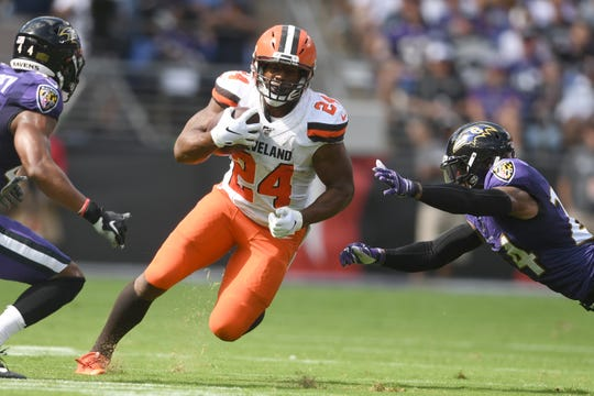Cleveland Browns running back Nick Chubb (24) carries the ball as Baltimore Ravens cornerback Brandon Carr (24) defends in the first quarter in a football game against the Cleveland Browns at M&T Bank Stadium.