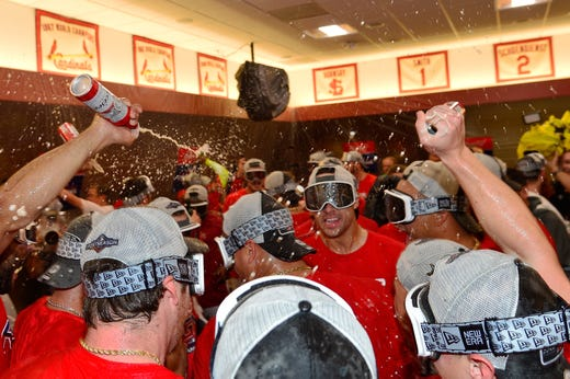 Cardinals players celebrate their NL Central title win with a 9-0 win against the Cubs.