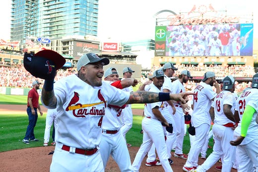 Cardinal catcher Yadier Molina leads the celebrations after winning the NL Central title.