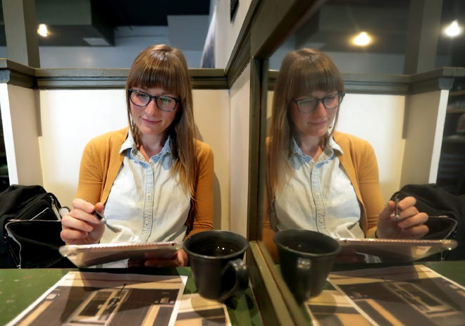 Appleton artist Emily Reetz works a project at Seth's Coffee in Little Chute late last month. Reetz illustrates buildings, landmarks and skylines around the Fox Cities.