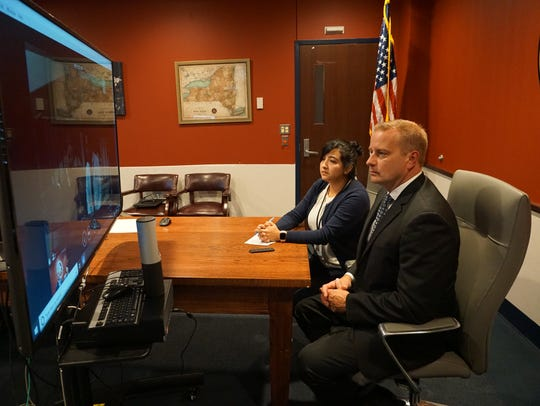 Broome County District Attorney Steve Cornwell, seated right, tests out a video livestream with an interpreter for Orlando Tercero's trial in Nicaragua.