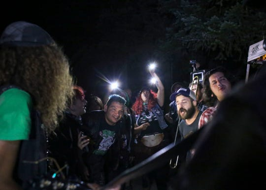 Others at Punx in the Woods lean in and sing along to the Truck Bed Boys' unplugged performance on Sept. 1.