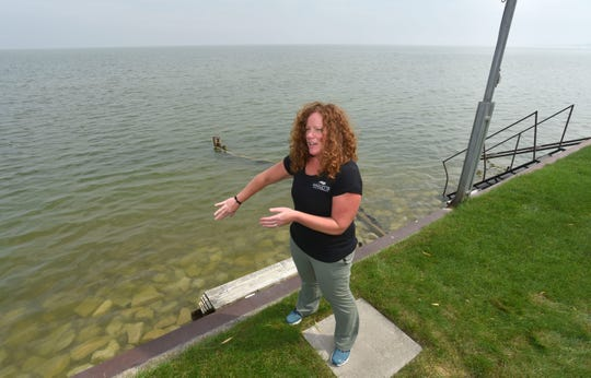Killarney Beach resident Julie Schultz of Bangor Twp. talks about the rising waters of Saginaw Bay as she stands on the seawall behind her house. She says her beachfront was three times larger when she and her family moved here years ago.