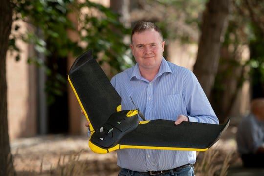 Dr. Jon Carroll, assistant professor of anthropology at Oakland University, holds a fixed wing drone that he uses for agricultural and irrigation research. Carroll has used the drone in Malawi to help farmers with irrigation needs that also can help control mosquito populations.