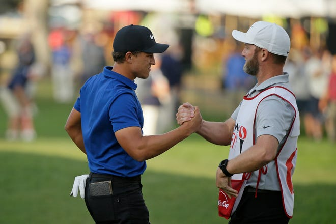 Cameron Champ is greeted by his caddie, Kurtis Kowaluk on the 18th green after winning the Safeway Open.