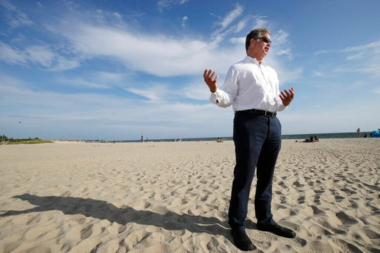 In this Aug. 21, 2019 photo, Andrew Gottlieb, executive director of the Association to Preserve Cape Cod, stands on Covell Beach in Centerville, Mass. near where the Vineyard Winds' proposed buried energy cables would stretch from offshore wind turbines, through the ocean, under the sand and parking lot, to a landing point onshore. The cables would then extend to a grid connection point inland.