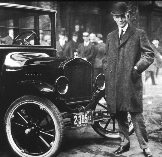 "Henry Ford stands beside a Model T in 1921. The model ""for the ordinary man"" was introduced on Oct. 1, 1908.  About one million Model T's were produced in 1921, and more than 15 million by the time production ended in 1927."