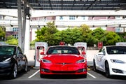 In this Tuesday, July 23, 2019 photo, a Tesla vehicle is parked at a new Tesla Supercharger station in Las Vegas. Analysts at Credit Suisse and RBC Capital Markets are among those predicting Tesla will post lower revenue for the third quarter than a year ago.