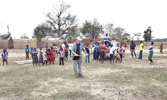 Oakland University Professor Jon Carroll has a crowd of onlookers as he prepares to fly a drone over the the Bwanje Valley Irrigation Scheme in Malawi, Africa. The drone's aerial images will help both in managing irrigation and in detecting stagnant pools where mosquitoes can breed and spread malaria.