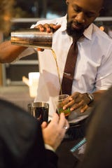 Bartender KaTrell Thomas pours a drink at a previous Detroit Cocktail Classic.