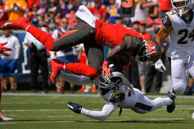 Tampa Bay Buccaneers wide receiver Chris Godwin, top, is tackled by Los Angeles Rams safety Eric Weddle during the first on Sunday.