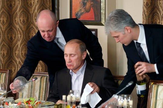 Businessman Yevgeny Prigozhin, left, serves food to Russian Prime Minister Vladimir Putin, center, during dinner at Prigozhin's restaurant outside Moscow, Nov. 11, 2011.