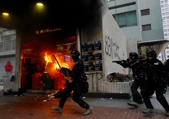 Riot police arrive after protesters vandalize in Hong Kong, Sunday.