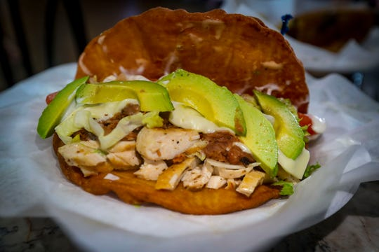 The Bonita Sandal from Rey's Island Grille features fried dough with steak or chicken, lettuce, tomato, queso blanco, refried beans, avocado and sour cream.