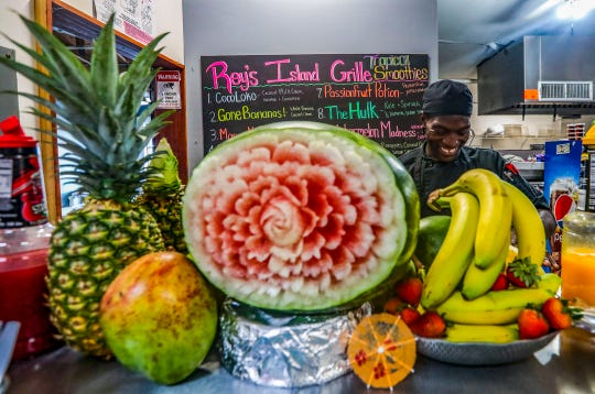 Darion Gunzarly carved intricate patterns into a watermelon at Rey's Island Grille. The flea-market stand offers fresh smoothies, along with a range of Caribbean and American dishes.