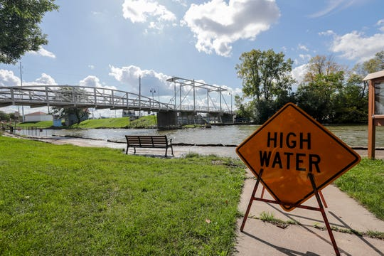 A sign warns of high water September 25, 2019, near the Fox River at Voyageur Park in De Pere, Wis. Record rainfall has forced the U.S. Army Corps of Engineers to increase the amount of water flowing from Lake Winnebago through dams on the Lower Fox River.