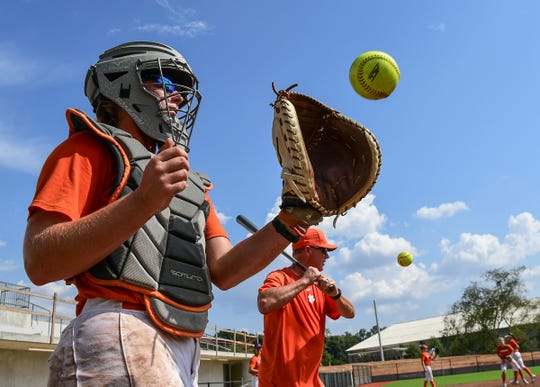 Clemson softball catcher Abby Stuart catches a ball near head coach John Rittman hitting infield grounders, during the first practice on their new field in Clemson Monday, September 30, 2019.