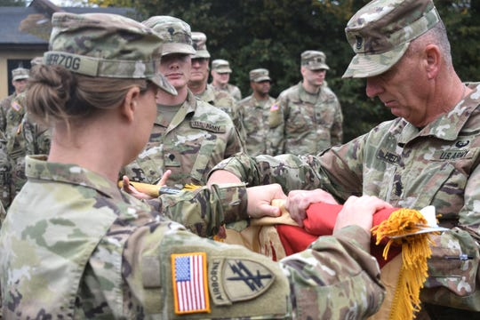 U.S. Army Reserve Col. Erica Herzog, left, commander of the 652nd Regional Support Group, and Command Sgt. Maj. Duane Hedrick, the 652nd command sergeant major, uncase the unit colors during a ceremony September 30 at Powidz Air Base, Powidz, Poland. The Soldiers arrived in Poland September 26 to begin a mobilization to Poland where they will be the first Army Reserve unit responsible for the operations of 10 base camps throughout the country. (U.S. Army Reserve photo by Master Sgt. Ryan Matson, 652nd Regional Support Group)