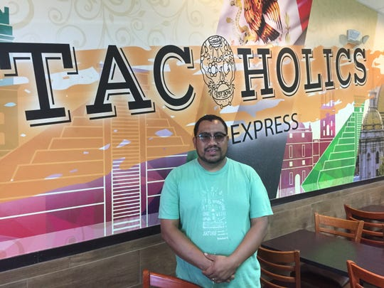 Marcos Nicolas poses in front of the interior wall of his new Henderson restaurant, which is called Tacoholics Express.