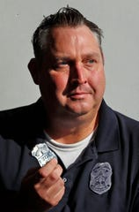 """IMPD Officer Eric Strange shows his old IPD badge on Sept. 27, 2019.  He took the guns from Kenneth Anderson just months before Anderson went on a shooting spree that claimed the life of Officer Timothy """"Jake"""" Laird, Anderson's mother, and left multiple officers wounded. After years of silence, Strange spoke out about the incident. He wants to fight for the establishment of red flag laws nationwide to prevent incidents like this."""