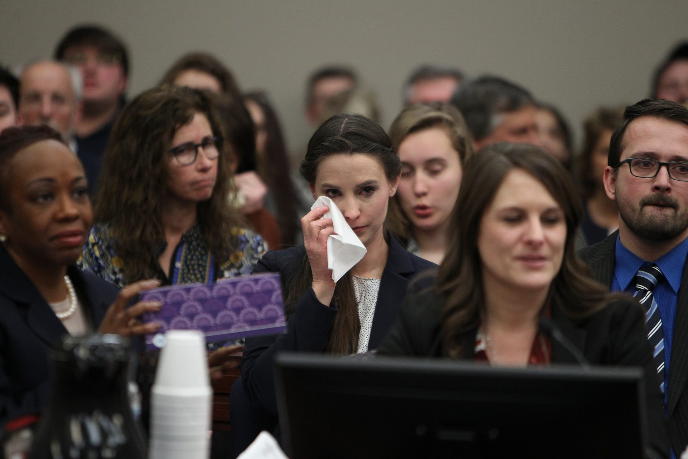 In this Jan. 24, 2018 photo, Rachael Denhollander wipes a tear from her eye as Larry Nassar, who admitted molesting some of the nation's top gymnasts for years, is sentenced, during the sixth day of victim impact statements in Ingham County Circuit Court in Lansing, Mich.