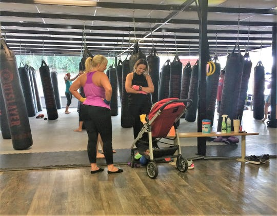 One of the benefits of a workout at Total Fitness Kickboxing for Kara Capalbo, right, of Powell is to spend some time enjoying 6-month-old Landyn Chandler.