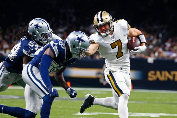 New Orleans Saints quarterback Taysom Hill (7) carries against Dallas Cowboys middle linebacker Jaylon Smith (54) and cornerback Anthony Brown (30) in the second half of an NFL football game in New Orleans, Sunday, Sept. 29, 2019. (AP Photo/Butch Dill)