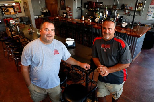 Terry Shirk, left, and Kerry Shirk stand in the bar portion of the Shirky's Pizza Zone in Carroll. The twin brothers bought the pizza restaurant in 2007. The location has been pizza shop since the 1970s.